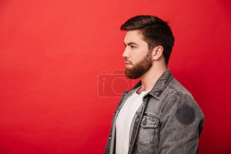 Portrait in profile of concentrated man 30s in jeans jacket look
