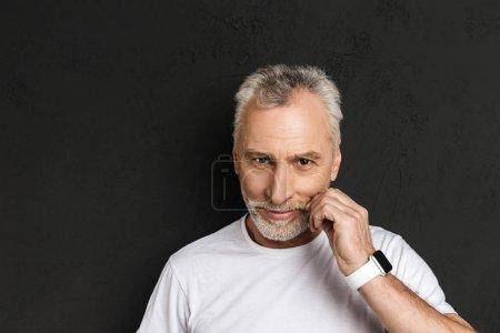 Photo pour Image d'un bel homme mûr debout isolé au-dessus d'un mur noir. Caméra de regard . - image libre de droit