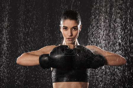 Photo for Strong fitness woman fighter 20s in sportswear keeping black boxing gloves together while training under rain drops isolated over dark background - Royalty Free Image
