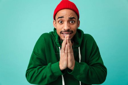 Portrait of a young afro american man in hat begging