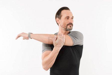 Photo pour Portrait d'un sportif mature confiant, faire des exercices d'étirement isolés sur fond blanc - image libre de droit