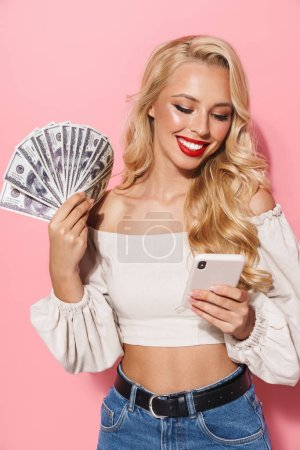 Photo for Image closeup of happy seductive woman wearing red lipstick holding cash money and cellphone isolated over pink background - Royalty Free Image