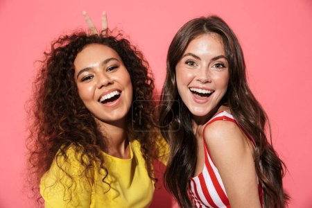 Photo for Two cheerful young girls wearing summer clothing standing isolated over pink background, laughing - Royalty Free Image