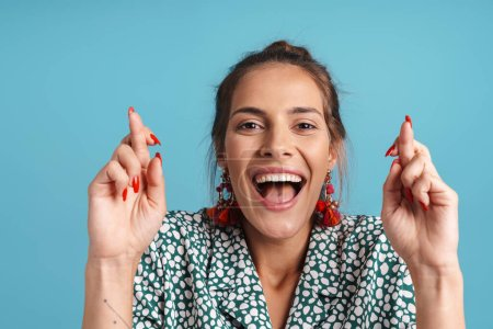 Photo for Close up portrait of a lovely happy young woman wearing shirt and bright earrings standing isolated over blue background, holding fingers crossed for good luck - Royalty Free Image