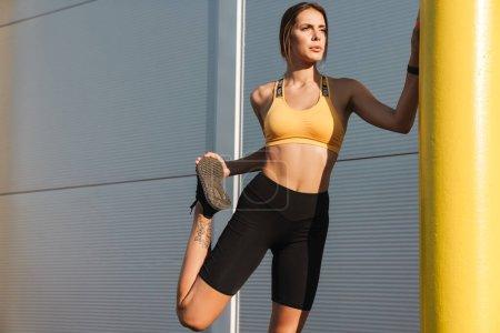Photo pour Image de la femme active en vêtements de sport étirant son corps tout en faisant de l'entraînement à l'extérieur - image libre de droit