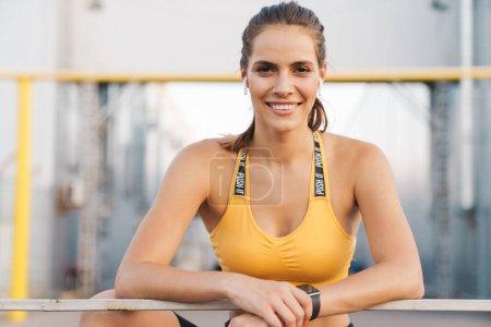 Photo pour Image de femme adorable en vêtements de sport avec des écouteurs souriants tout en se tenant debout sur la rampe à l'extérieur - image libre de droit
