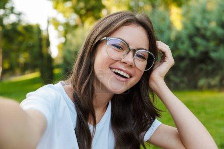 Photo pour Gros plan d'une jolie fille souriante assise au parc, prenant un selfie - image libre de droit