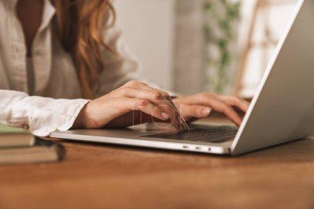 Photo pour Photo agrandie d'une jeune femme d'affaires au gingembre assise au bureau à l'aide d'un ordinateur portatif. - image libre de droit