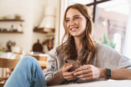 Photo pour Image de jeune jolie jolie jolie rousse à l'intérieur assise à la maison en utilisant un téléphone portable. - image libre de droit