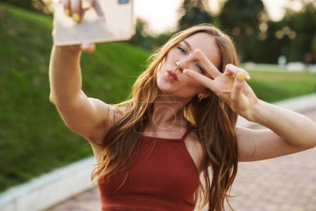 Photo pour Photo d'une jolie jeune femme gingembre se promenant dans un parc verdoyant en plein air se prendre par téléphone mobile. - image libre de droit