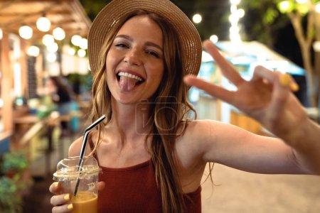 Photo pour Image d'une femme joyeuse, optimiste et positive, marchant dans la rue en buvant du jus le soir montrant la paix. - image libre de droit