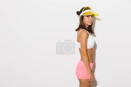 Photo pour Portrait de belle femme caucasienne portant un chapeau de visière debout et regardant la caméra isolée sur fond blanc - image libre de droit
