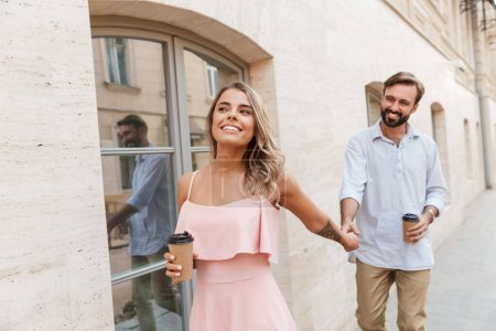 Photo for Photo of happy cheery cute young loving couple outdoors walking drinking coffee. - Royalty Free Image