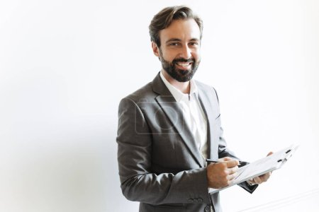 Photo pour Image d'un homme d'affaires souriant, vêtu d'un costume en bonne et due forme, tenant un presse-papiers et prenant des notes pendant qu'il travaille - image libre de droit