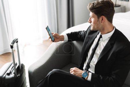 Photo pour Image d'un jeune homme caucasien portant un costume noir en bonne et due forme, assis sur un canapé avec téléphone intelligent et valise dans une chambre d'hôtel pendant un voyage d'affaires - image libre de droit