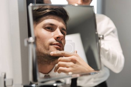 Photo pour Image close of handsome man wearing formal suit looking at mirror in bathroom at hotel room during business trip - image libre de droit