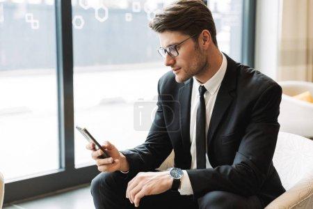 Photo pour Photo d'un beau jeune homme vêtu d'un costume et de lunettes noirs, assis à l'hôtel avec son téléphone intelligent pendant un voyage d'affaires - image libre de droit