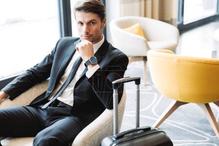 Photo pour Photo d'un jeune homme d'affaires non rasé vêtu d'un costume noir et d'une montre-bracelet assis dans le hall d'hôtel avec sa valise - image libre de droit