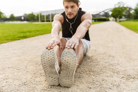 Foto von einem aktiven Mann, der mit Kopfhörern trainiert und bei gr