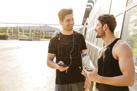 Foto starker Männer, die beim gemeinsamen Sport lächeln
