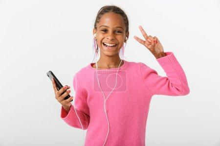Photo pour Image d'une Africaine américaine souriante tenant un téléphone cellulaire et un écouteur tout en montrant un signe de paix isolé sur fond blanc - image libre de droit