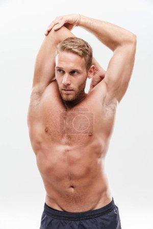Photo pour Beau jeune sportif concentré torse nu faisant des exercices d'étirement tout en étant isolé sur fond blanc - image libre de droit