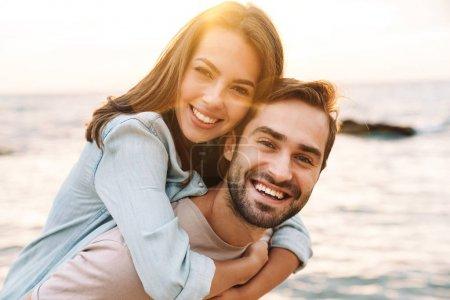 Photo pour Image d'un jeune homme heureux faisant un tour de piggyback belle femme et riant en marchant sur une plage ensoleillée - image libre de droit