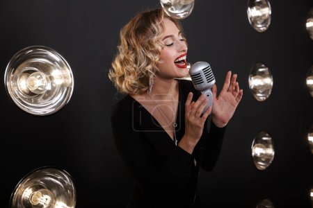 Photo pour Image of adorable artist woman in elegant dress singing into microphone over lights background - image libre de droit