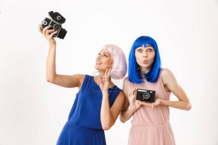 Photo pour Portrait of two joyful women wearing blue and pink wigs gesturing peace sign while using retro cameras isolated over white background - image libre de droit