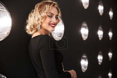 Photo pour Image of pleased blonde salope woman wearing elegant dress and jewelry smiling over lights background - image libre de droit