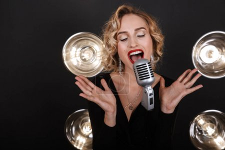 Photo pour Image of young artist woman in elegant dress singing into microphone over lights background - image libre de droit