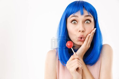 Photo pour Portrait of cute funny woman wearing blue wig holding lollipop and grimacing isolated over white background - image libre de droit
