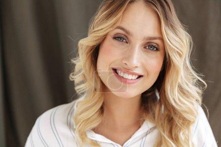 Foto de Cierre de una guapa rubia sonriente con camisa mirando a la cámara sobre la pared gris. - Imagen libre de derechos