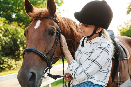 Photo pour Image of joyful young blonde woman wearing hat standing by horse at yard in countryside - image libre de droit