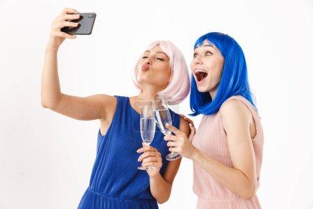 Portrait of two joyful women wearing blue and pink...