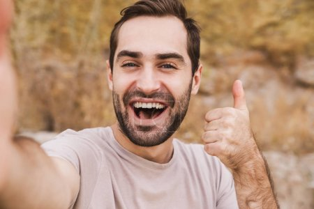 Photo pour Image of unshaven laughing man showing thumb up and taking selfie photo while walking on sunny beach - image libre de droit
