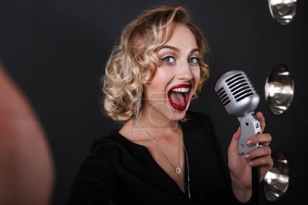 Photo pour Image of excited vocalist woman in elegant dress singing into microphone over lights background - image libre de droit