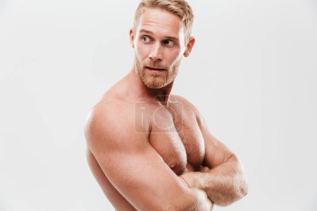 Photo for Handsome young concentrated shirtless sportsman standing with arms folded, looking away isolated over white background - Royalty Free Image
