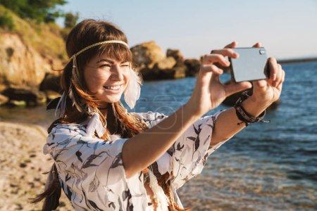 Photo pour Image d'une jolie hippie en bandeau de plumes prenant sa photo sur un téléphone portable au bord de la mer le matin - image libre de droit