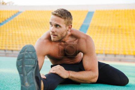 Bild von gut aussehenden hemdlosen Mann streckt seinen Körper bei Sport gr