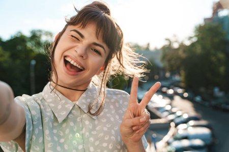 Photo pour Photo d'une jeune jolie femme heureuse et positive sur un balcon prendre un selfie par caméra montrant la paix . - image libre de droit