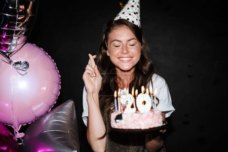 Photo for Image of caucasian funny woman in party cone holding cake and fingers crossed while smiling isolated over black wall - Royalty Free Image