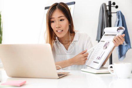 Photo for Smiling young asian businesswoman having a meeting on a video call while sitting at the workplace - Royalty Free Image