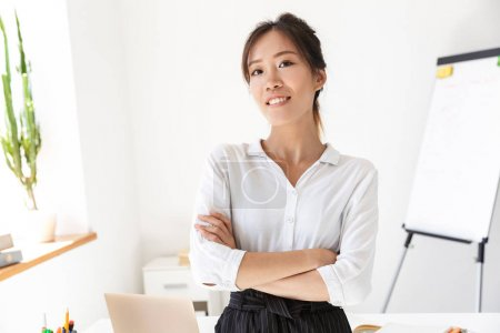 Photo for Confident attractive young asian businesswoman standing at her office, arms folded, looking at camera - Royalty Free Image