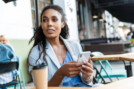 Photo for Attractive smiling young african businesswoman sitting at the cafe table outdoors, using mobile phone while drinking coffe in a takeaway cup - Royalty Free Image