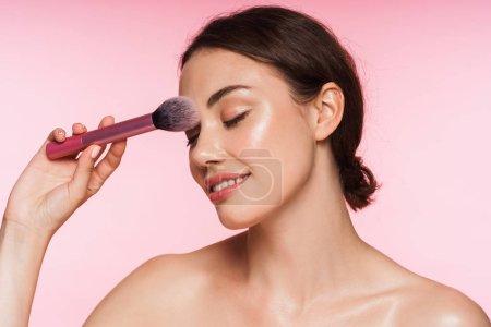 Photo pour Portrait de beauté d'une belle jeune brune toplesse et souriante, isolée sur fond rose, tenant le maquillage sur son visage - image libre de droit