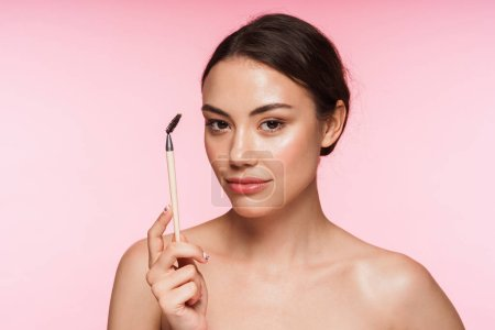Photo pour Portrait de beauté d'une belle jeune brune sans topless se tenant isolée sur fond rose, tenant un brosse à sourcils - image libre de droit