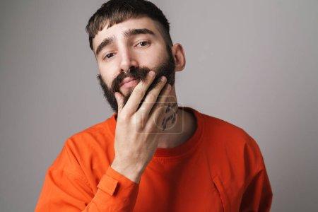 Photo pour Image gros plan de jeune homme non rasé avec des bijoux nez portant chemise orange touchant sa barbe isolé sur fond gris - image libre de droit