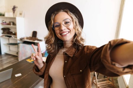 Photo for Image of joyful young woman in hat smiling and gesturing peace sign while taking selfie photo indoor - Royalty Free Image