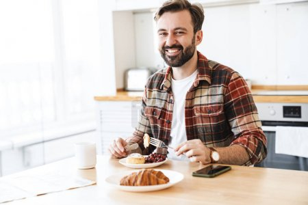 Photo for Portrait of joyful bearded man smiling and eating cake while having breakfast in kitchen at home - Royalty Free Image